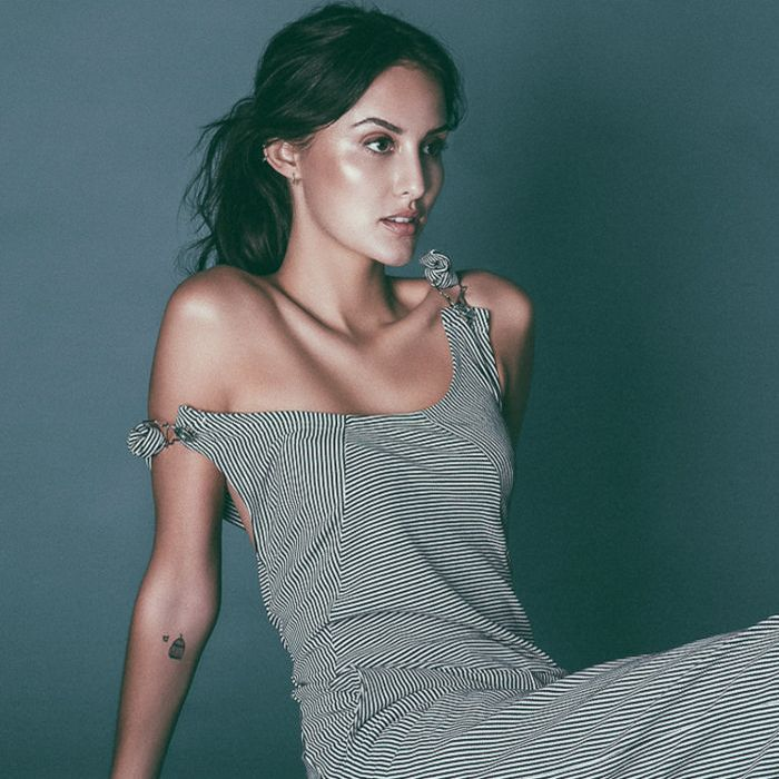 Lucy Watson sitting and posing in dress