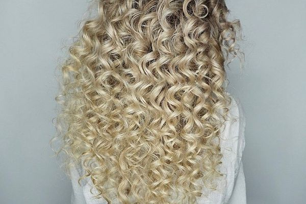 Woman with curly, toasted coconut-colored hair