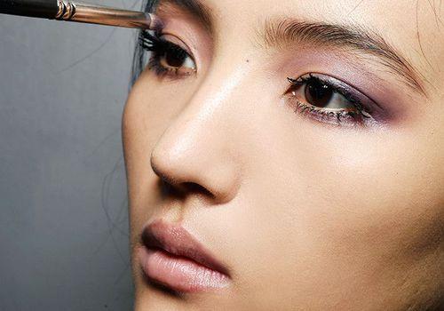 Woman having eyeshadow applied