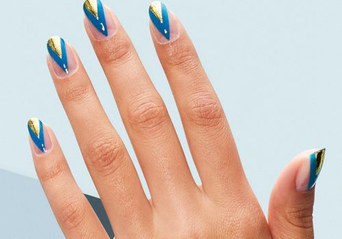 Person with gold and blue negative space nails.