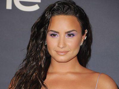 Demi Lovato long wavy hair with purple eyeshadow