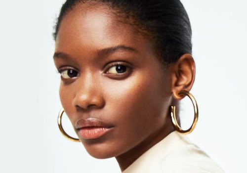woman with hair pulled back into a bun with hoop earrings