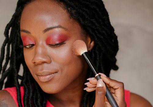 person applying highlighter to cheekbone