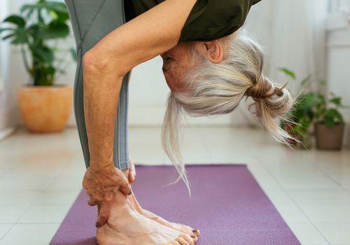 woman stretching on purple yoga mat