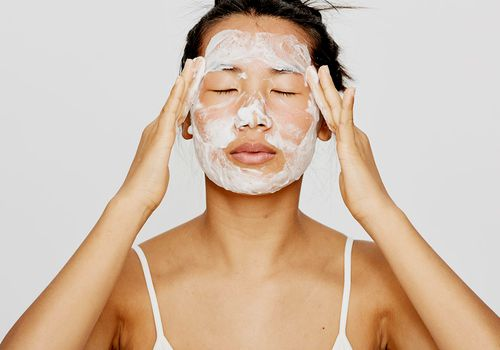 person washes face with cleanser