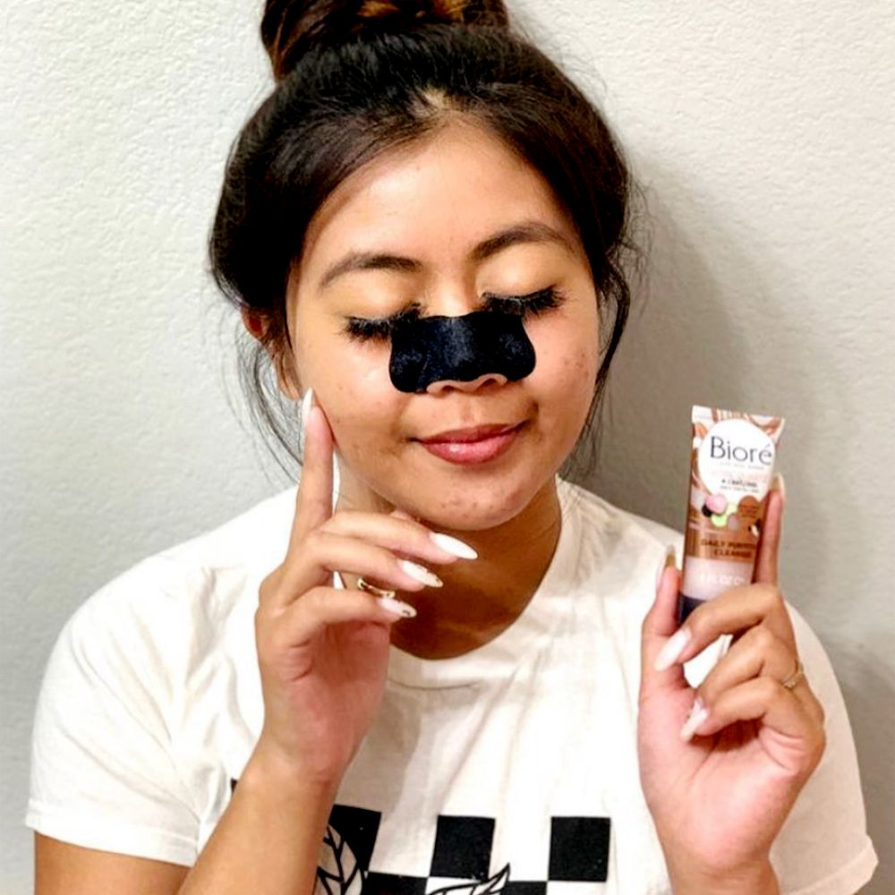 person with charcoal mask on face