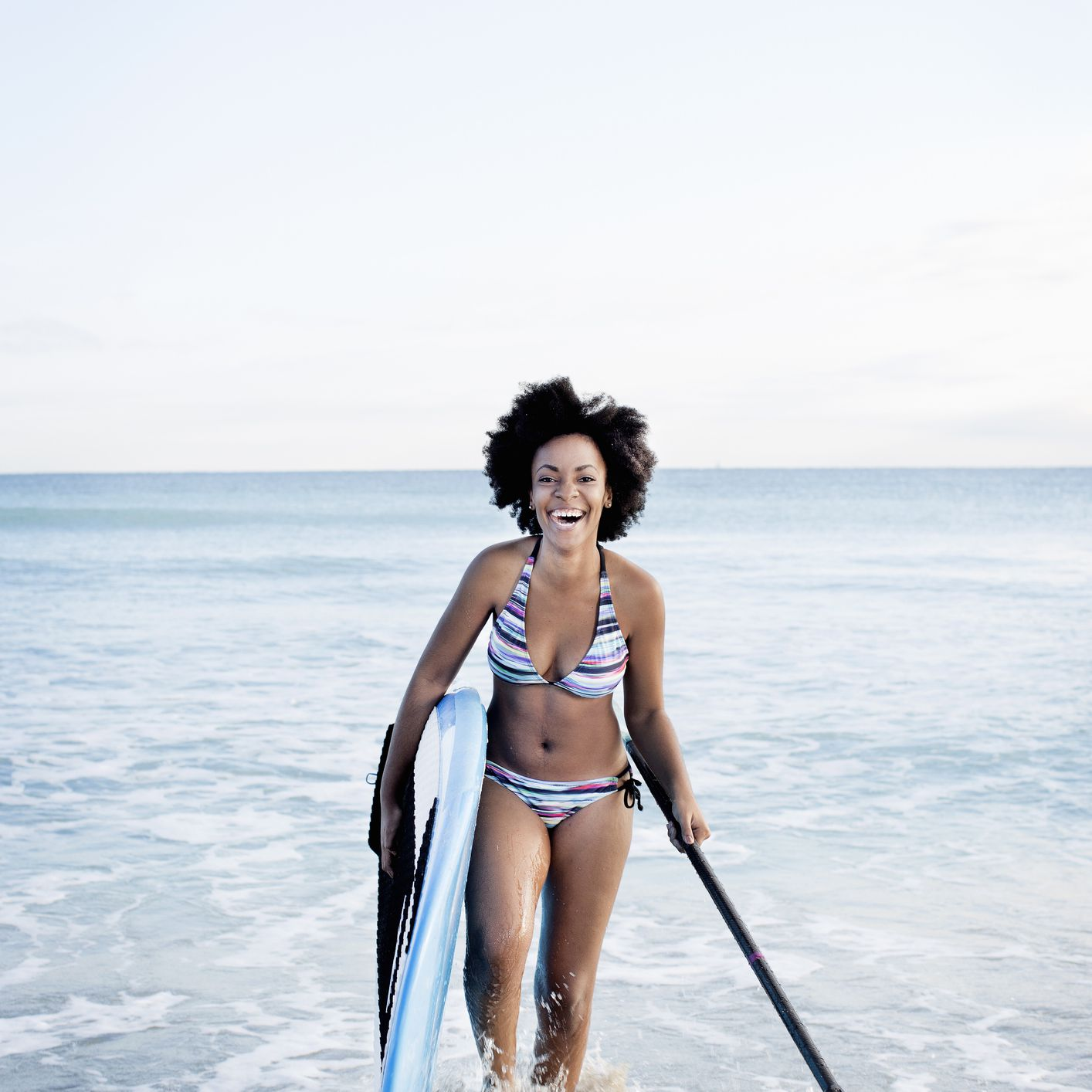 Black woman on beach with paddle board