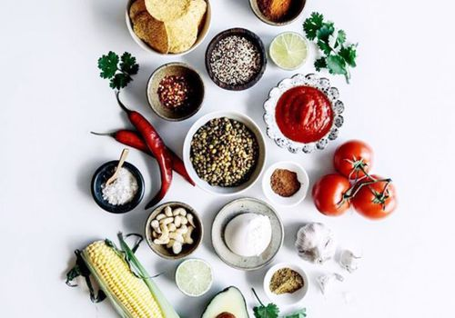 healthy groceries including tomatoes, quinoa, cocoa powder