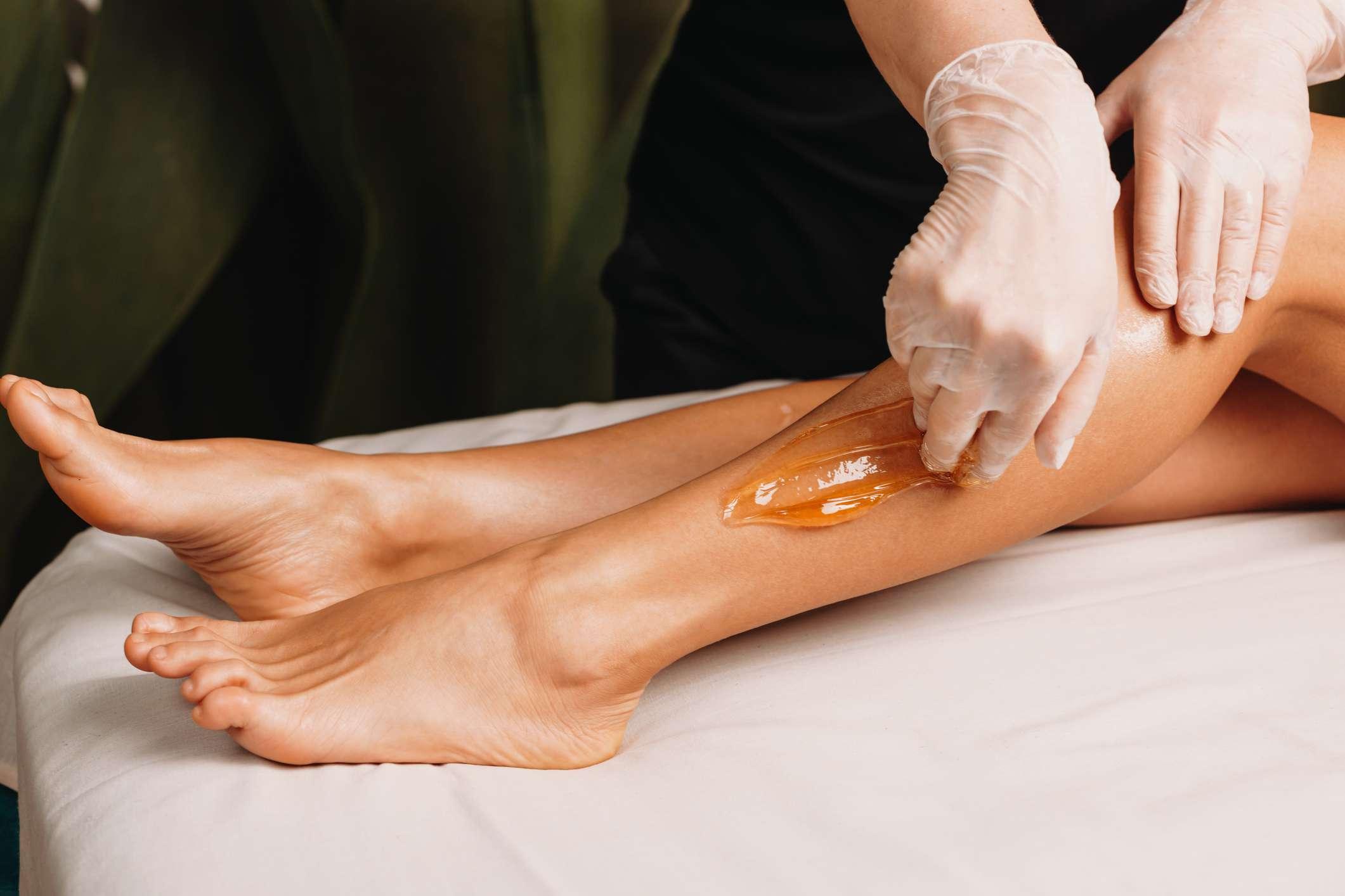 person getting their legs waxed
