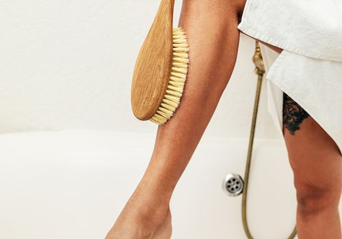 Person dry brushing their leg while standing in the shower.