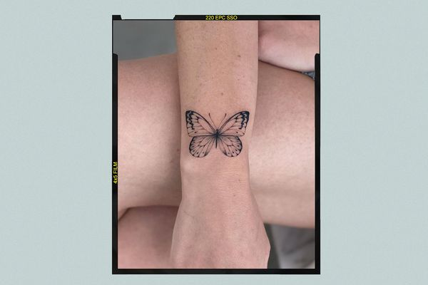 A forearm with a minimalistic butterfly tattoo