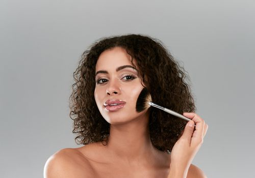 Woman With Curly Hair And A Highlighter Brush