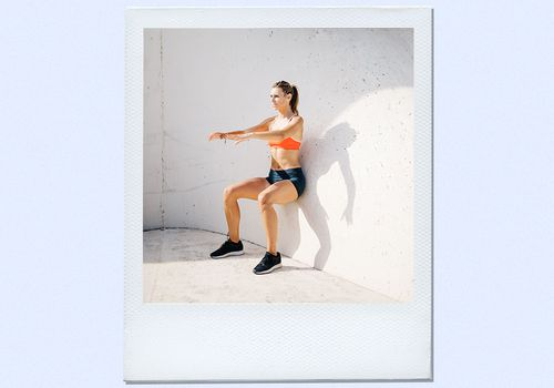 woman performing isometric exercise against wall