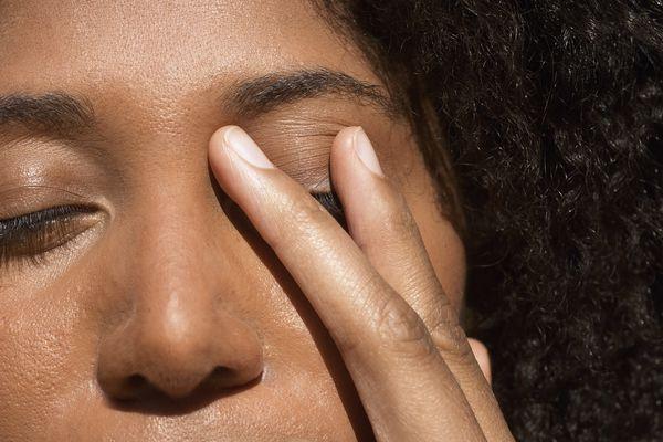 woman holding eye shut