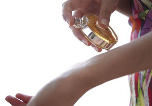 Woman spray perfume on wrist