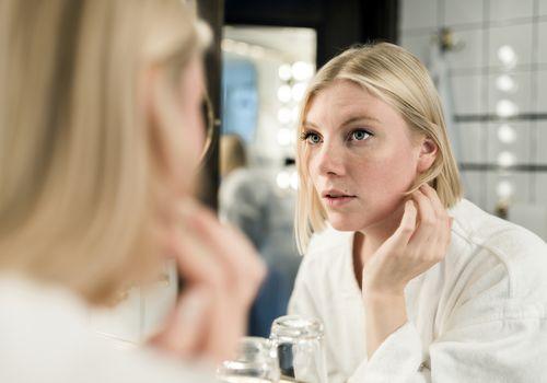 Woman examining face in bathroom mirror