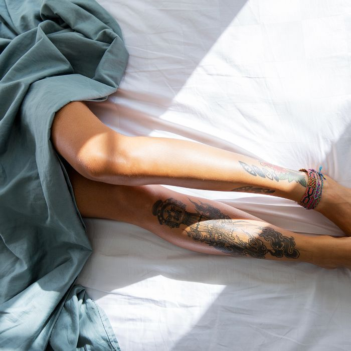 a45ae1161650bb Overhead view of a woman's tattooed legs sprawled out on a bed