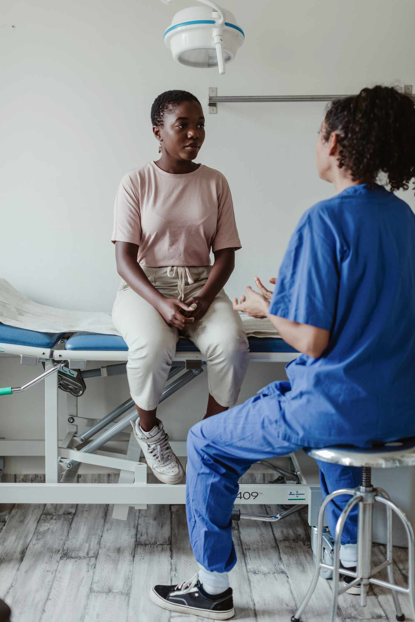 Black woman patient with woman doctor