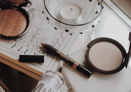Makeup products laying on a mirror