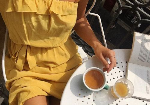 woman in yellow dress with tea and sunglasses