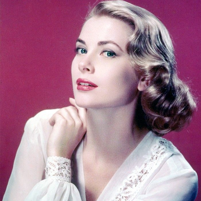 Grace Kelly wearing white blouse, sitting against purple background