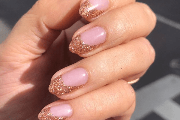 Person showcasing champagne-colored glitter tips on their nails.