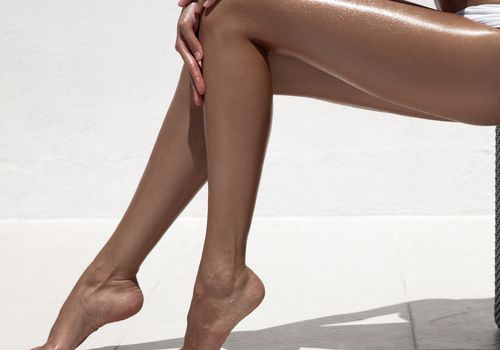 Woman's shiny, tan legs against a white background
