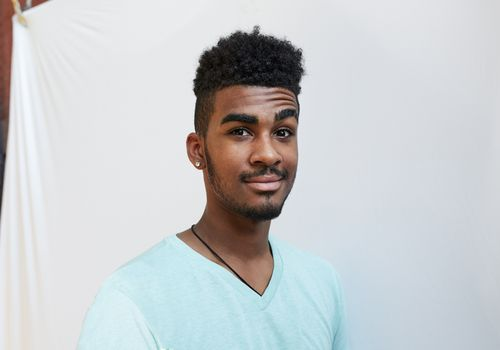 Black man wearing a turquoise v-neck with an eyebrow raise