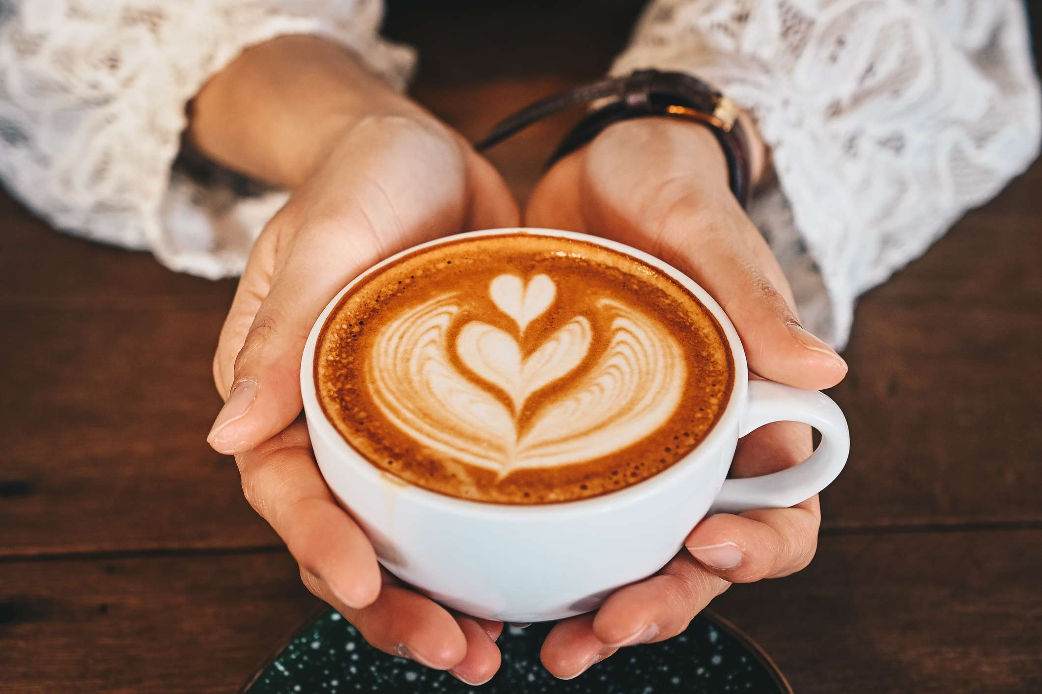 Cropped shot of woman hands holding a cup of hot latte coffee in her hands
