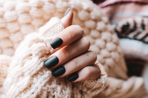 dark green nails against cream fabric