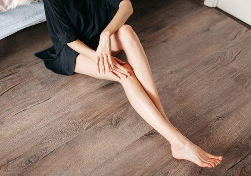 Woman in black robe massaging legs while sitting on wood floor