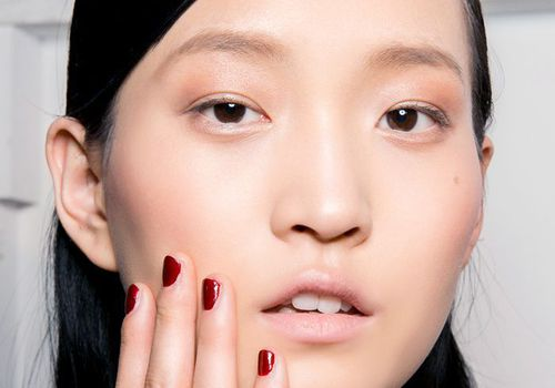 model with minimal makeup and red nail polish touching face