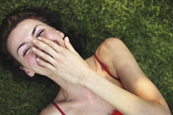 woman laughing in grass