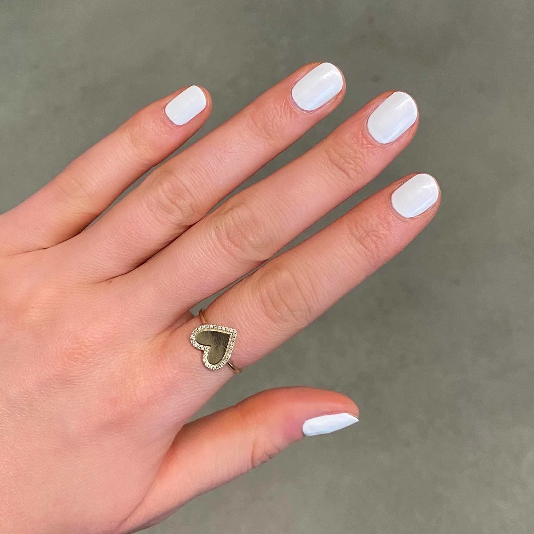 Hand with plain white nails and a heart ring.