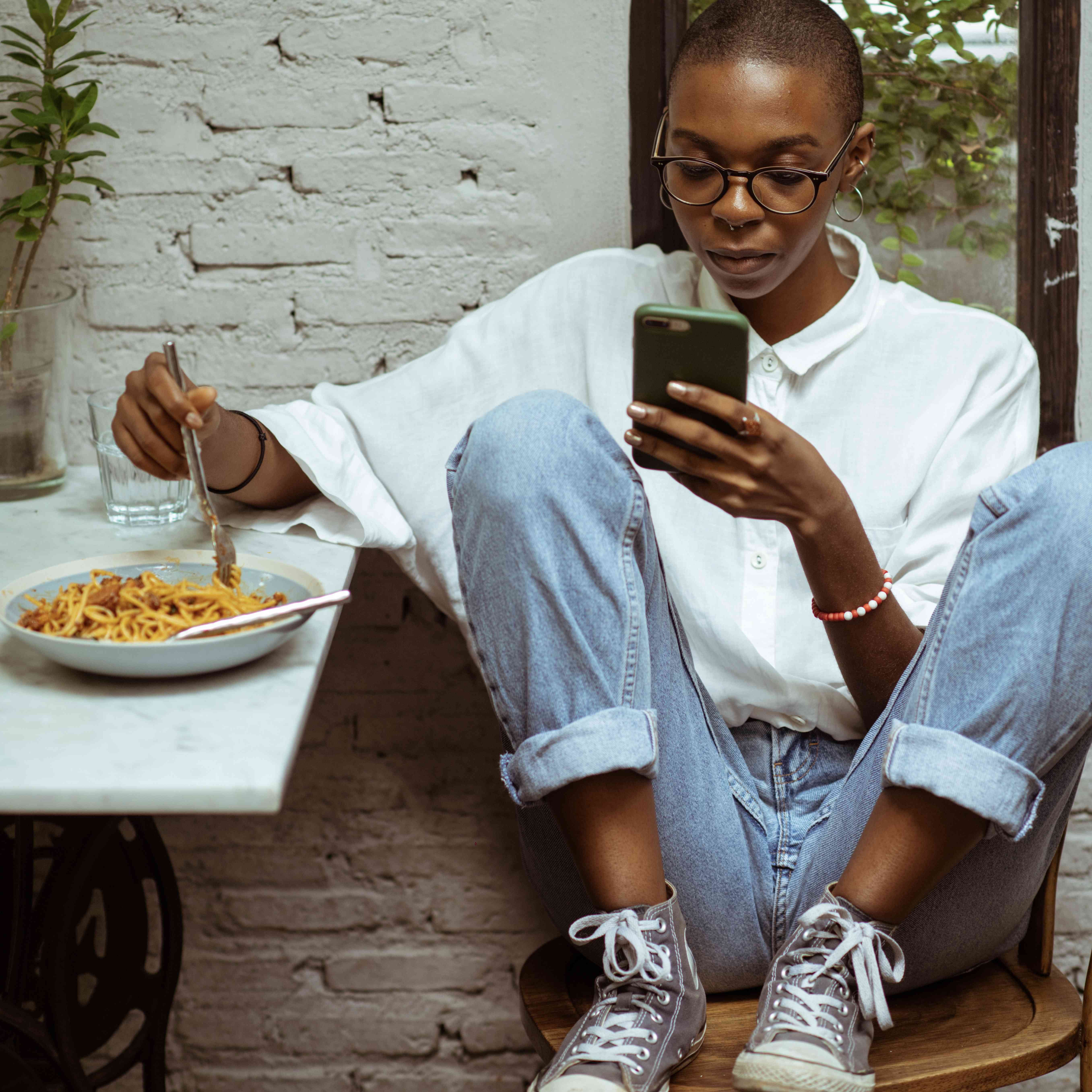 Woman eating pasta on phone