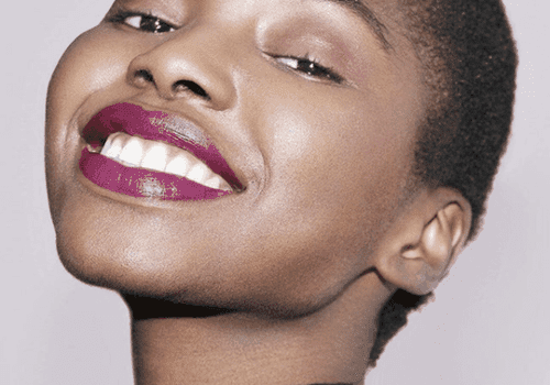 woman with purple lipstick smiling