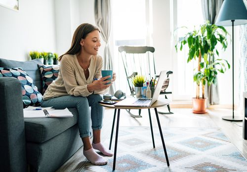 woman holding mug looking at laptop in living room