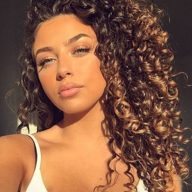 Model with curly hair and soft brown highlights
