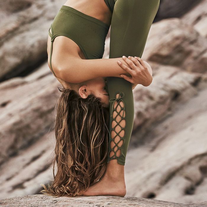 What is yoga: woman practicing yoga on a rock