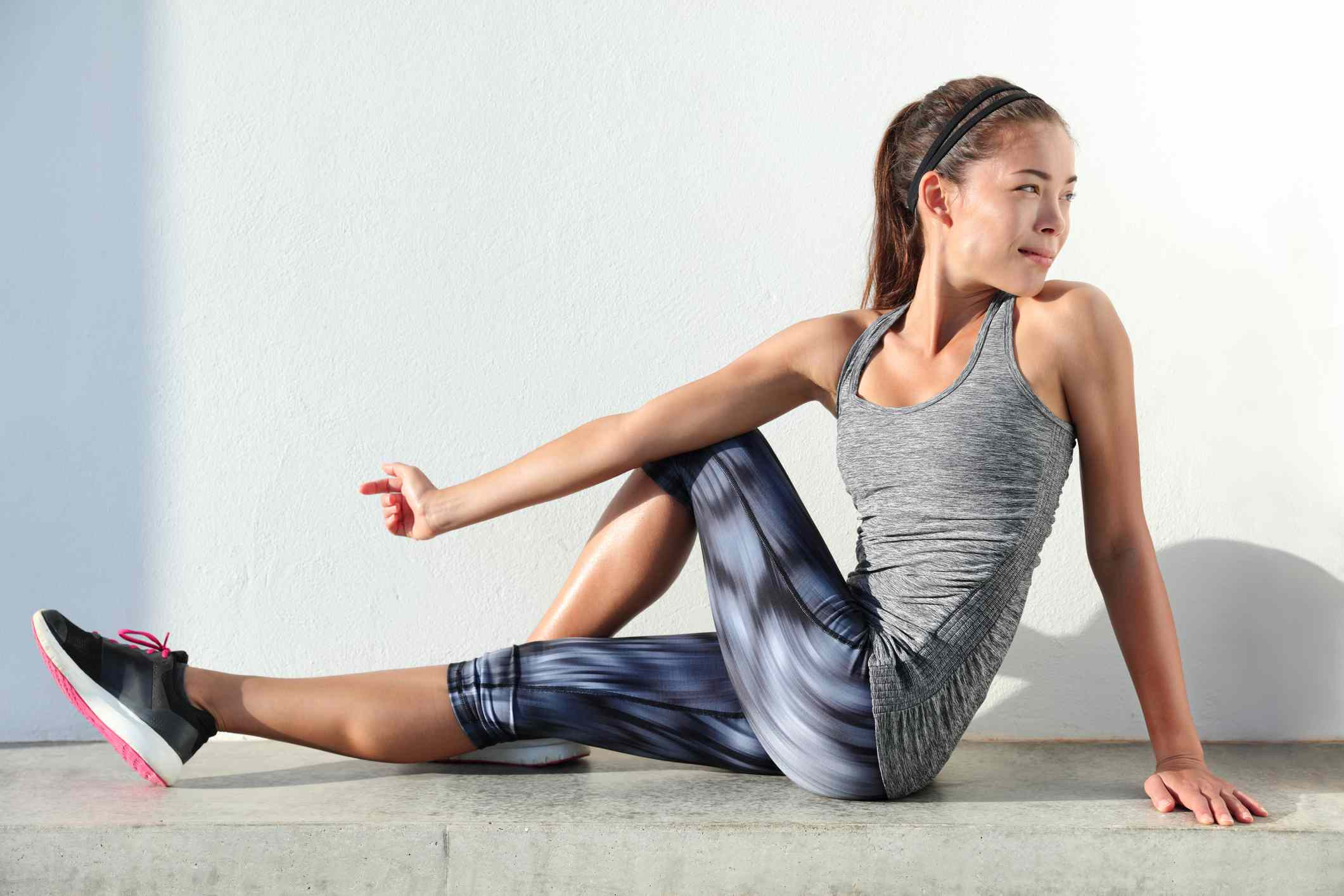 Fitness woman stretching legs doing pilates leg stretches exercises