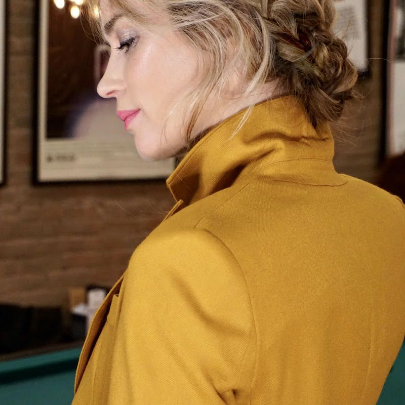 Emily Blunt gold jacket, braids, and pinks lips