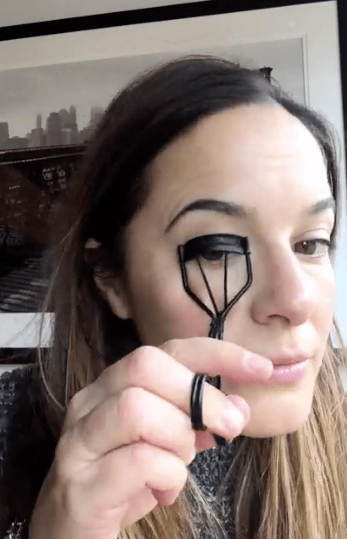 Makeup artist Jenna Menard curling her eyelashes