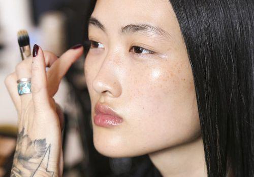 Makeup artist applying concealer to model's face