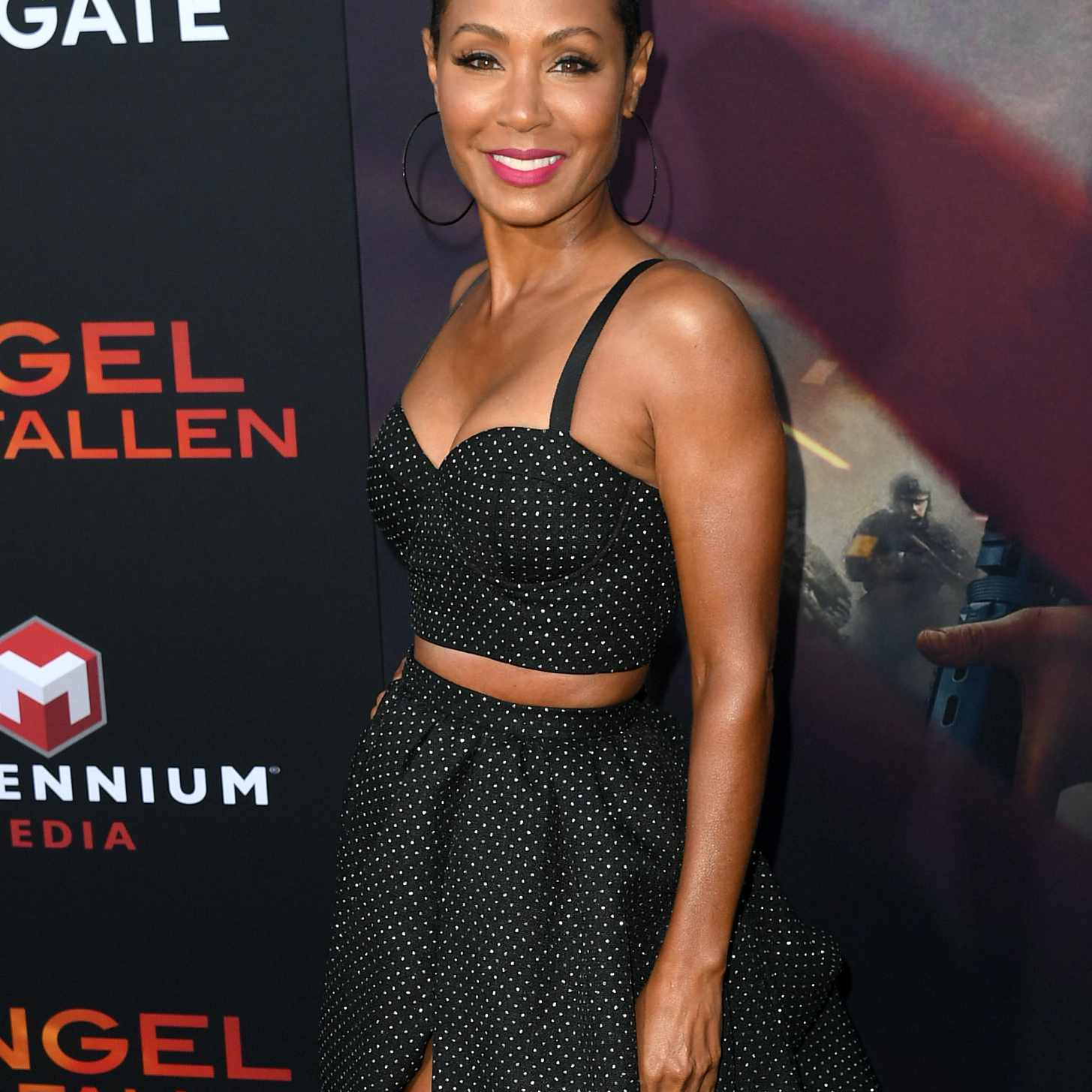Jada Pinkett-Smith wearing a black dress on the red carpet of Lionsgate's
