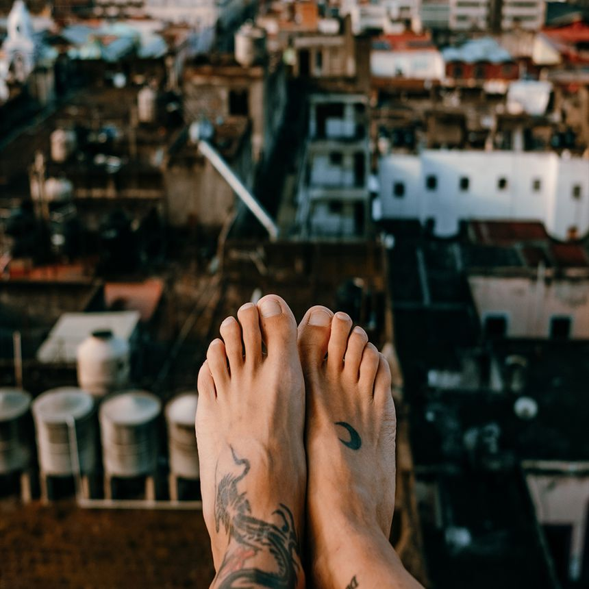closeup of feet hanging off roof and city below