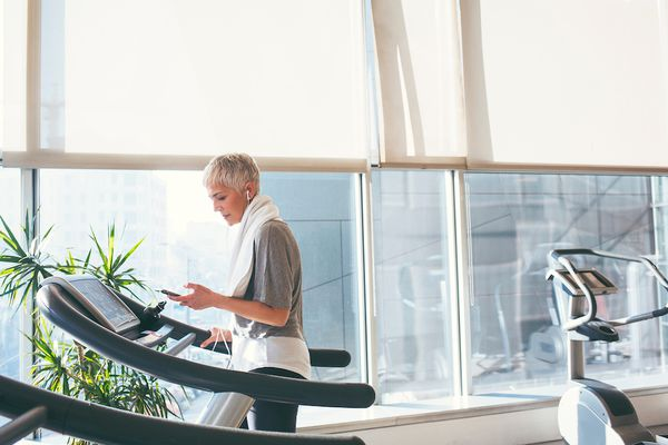woman on a treadmill, looking at her phone