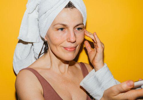 woman in 40s applying skincare