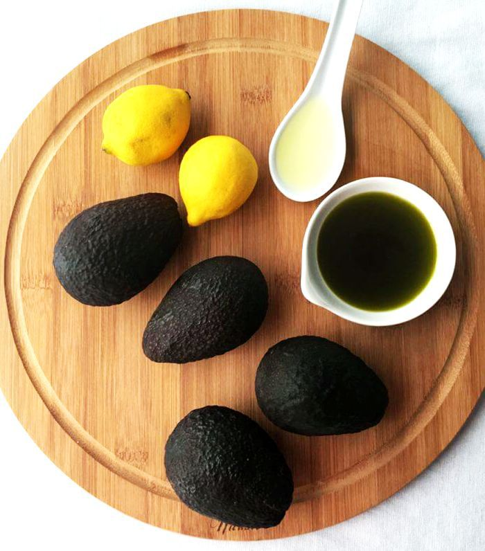 Avocado, hemp oil, and lemon on a round wooden cutting board
