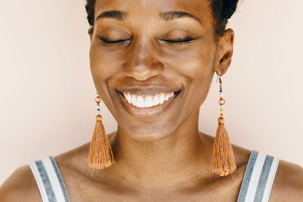 woman smiling with her eyes closed