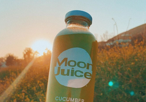 moon juice being held in the air against a sunset